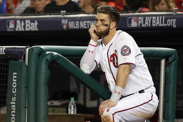 WASHINGTON, DC - OCTOBER 7: Bryce Harper #34 of the Washington Nationals looks on from the dugout against the Los Angeles Dodgers during the seventh inning in game one of the National League Division Series at Nationals Park on October 7, 2016 in Washington, DC. (Photo by Rob Carr/Getty Images)